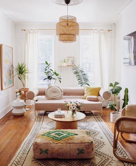 Boho-chic living area with plants, colourful rug, cane furniture and timber floors.