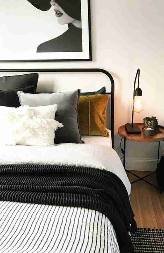 Bedroom with black bed frame, artwork, lamp, cushions and throw.