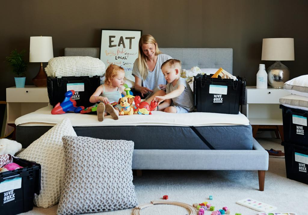 Mother on bed with children, surrounded by packing boxes.